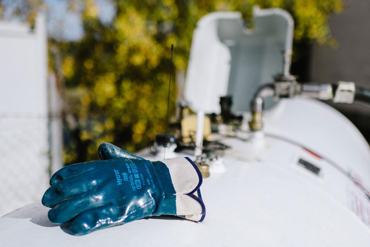 Handschuhe auf Flüssiggas Tank